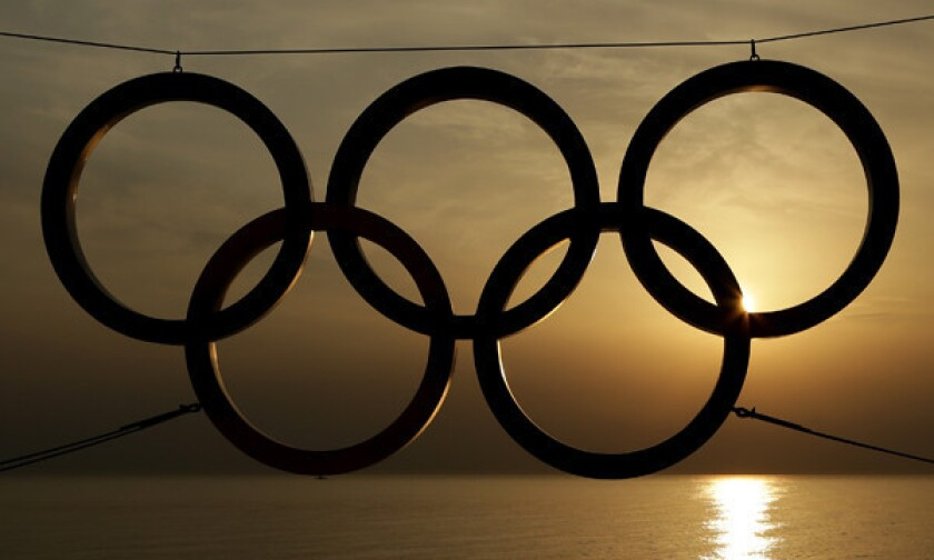 The sun sets on the Black Sea in Sochi, Russia, beyond an Olympic rings display.