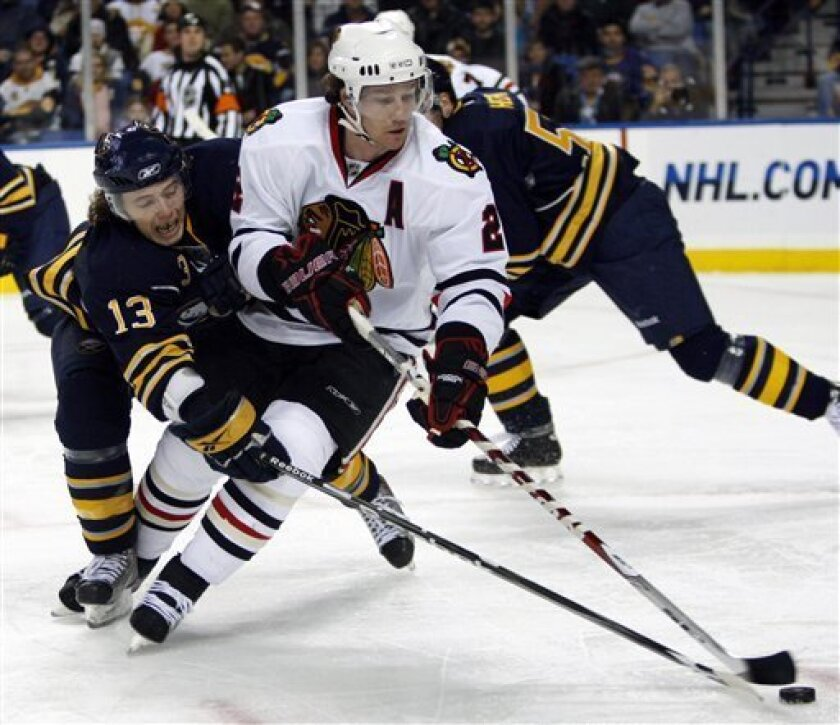 Buffalo Sabres' Tim Kennedy (13) battles for the puck with Chicago Blackhawks' Duncan Keith (2) during the first period of an NHL hockey game in Buffalo, N.Y., Friday, Dec. 11, 2009. (AP Photo/ David Duprey)