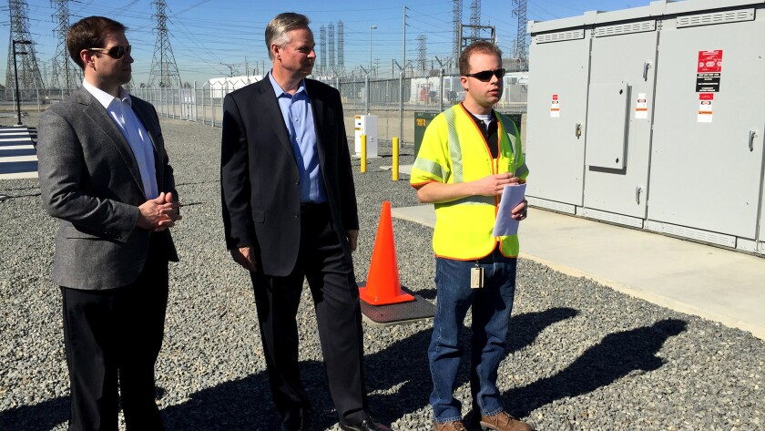 J.B Straubel, left, Tesla's chief technology officer, and Kevin Payne, Southern California Edison's CEO, provide a tour with a utility worker of Tesla's energy storage system at Edison's Mira Loma substation in Ontario.