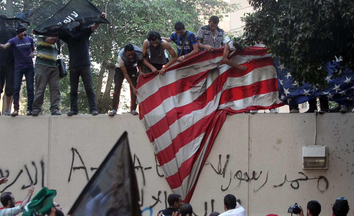 Egyptian protesters take away the U.S. flag in front the U.S. Embassy in Cairo. The demonstrators are angry over a video they say defames the prophet Muhammad.