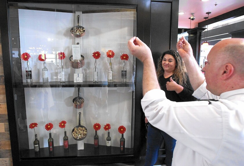 Chef Laurent Brazier of Bistro Papillote, right, shows his appreciation of the store window created by OCC design student Madison Alvarez and her team, who gives a thumbs up for first place design at the South Coast Collection student merchandise window design project on Wednesday.