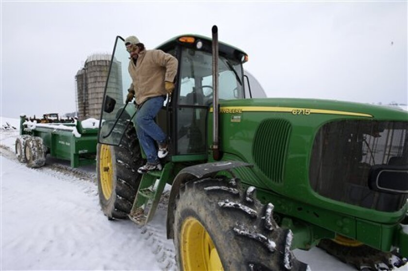 In this Saturday, Jan. 26, 2013 photo, Shawn Georgetti climbs out of his John Deere tractor on his 167-acre family dairy farm in Avella, Pa. With royalties from a Range Resources gas well on his property, Georgetti has been able to buy newer farm equipment that's bigger, faster, and more fuel-effic