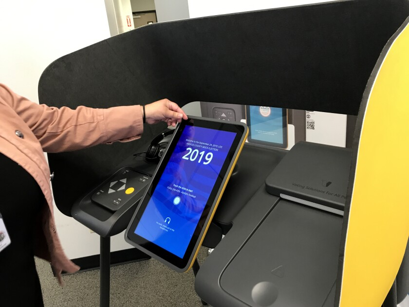 A county registrar staffer in Norwalk shows off the touch screen on one of Los Angeles County's interactive ballot-marking machines.