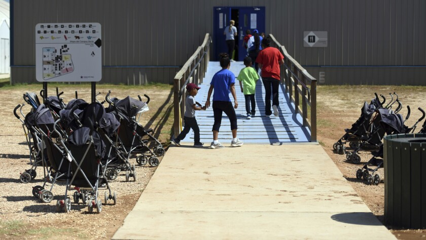 In this Aug. 9, 2018, photo, provided by U.S. Immigration and Customs Enforcement, immigrants walk into a building at South Texas Family Residential Center in Dilley, Texas.