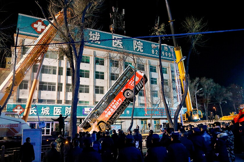 A crane is used to lift a bus out of a sinkhole Jan. 13 in the city of Xining in northwestern China.