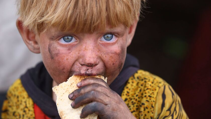 A displaced Syrian child, who fled the countryside surrounding the Islamic State group stronghold of Raqqa, eats at a temporary camp in the village of Ain Issa on May 2, 2017.
