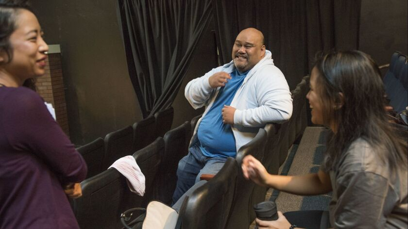 Playwright Boni B. Alvarez's laughs with cast members of his show, ?America Adjacent,? which is bein