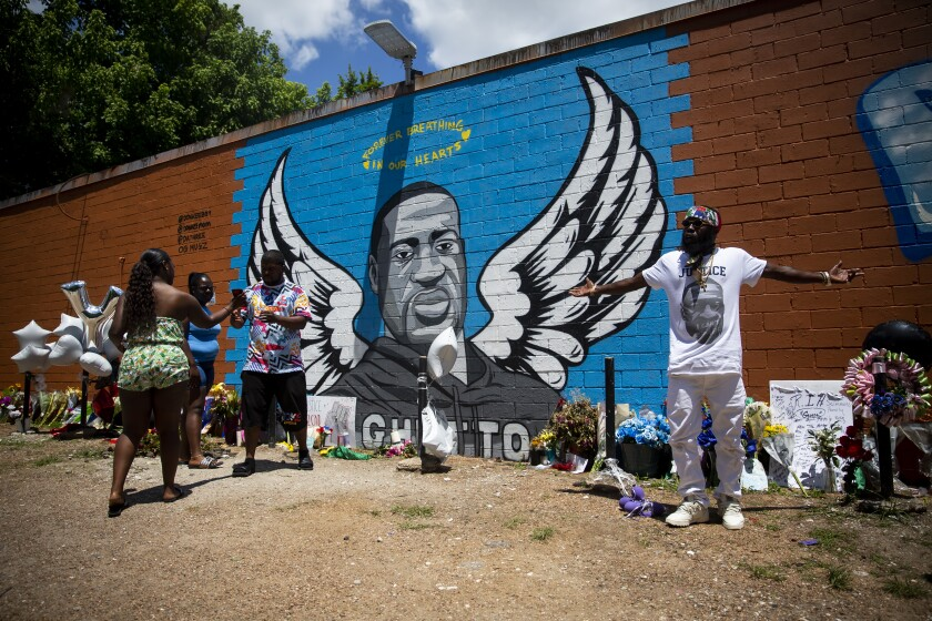 OG Bezel, right, joins other visitors at the mural honoring George Floyd in the Third Ward in Houston on June 7, 2020.