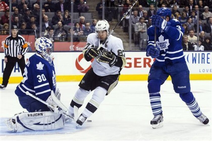 Pittsburgh Penguins' Sidney Crosby, center, skates in on Toronto Maple Leafs goaltender Ben Scrivens as Leafs' Dion Phaneuf defends during the first period of their NHL hockey game, Thursday, March 14, 2013, in Toronto. (AP Photo/The Canadian Press, Chris Young)