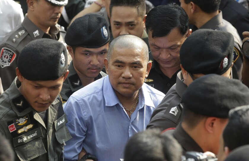 Thai policemen escort fortune teller Suriyan Sucharitpolwong, center, better known by the nickname Mor Yong, as he arrives at military court in Bangkok, Thailand, on Oct. 21, 2015. Suriyan died while in custody over the weekend.