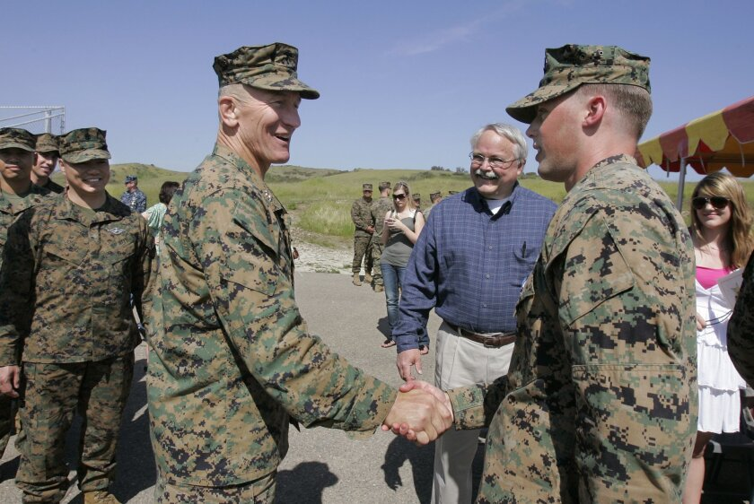 Navy Petty Officer 3rd. Class Peter A. Gould shakes hands with Marine Major General Michael Regner after the ceremony where Gould received the Silver Star Medal for heroism in Afganistan. The man in the background is Peter's father Joe Gould. Regner is the Commanding Officer of the 1st. Marine