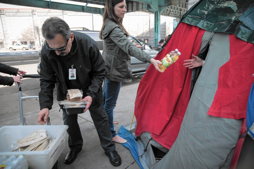 Wayne Garcia and Mary Walker of HealthRIGHT 360 distribute food to homeless people camped under the 101 Freeway in San Francisco.