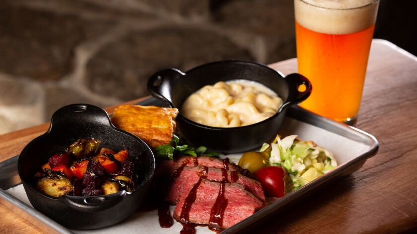 A barbecue plate with roasted vegetables and macaroni and cheese alongside a California craft beer f