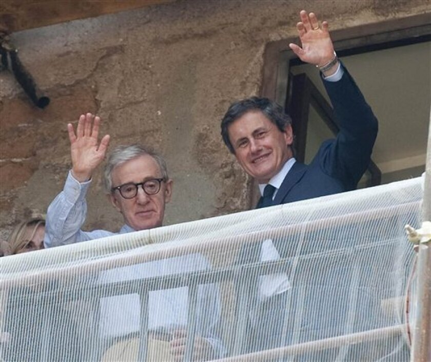 """US director Woody Allen, left, and Rome's Mayor Gianni Alemanno gesture to photographers from Rome's Campidoglio, Capitol Hill, balcony overlooking the Roman forum, Wednesday, July 6, 2011. It was not Woody Allen's beloved Manhattan skyline, but the American filmmaker was treated to a beautiful view of Rome's ancient ruins when he met with the city's mayor. Allen is in Rome to shoot his next movie, """"The Bop Decameron."""" The comedy will feature Roberto Benigni, Jesse Eisenberg, Ellen Page, Penelope Cruz and Judy Davis, among others. (AP Photo/Virginia Farneti, LaPresse) ITALY OUT"""