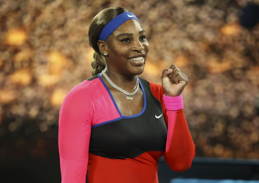 Serena Williams smiles and holds up a fist