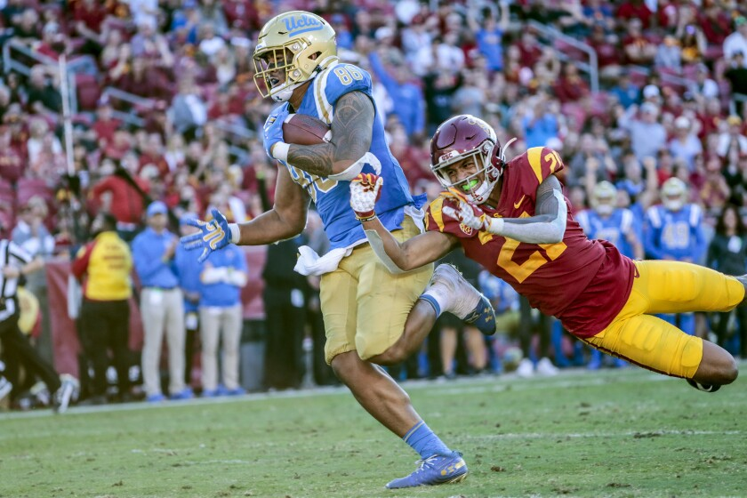 UCLA tight end Devin Asiasi runs past USC safety Isaiah Pola-Mao for a third quarter touchdown at the Coliseum on Nov. 23, 2019.