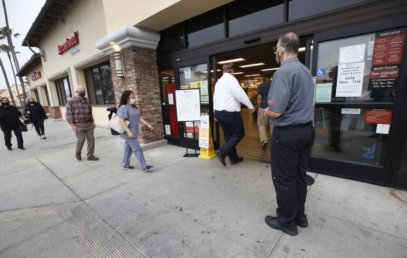 Vons supervisor Anthony Capone, right, greets shoppers in Torrance in April.