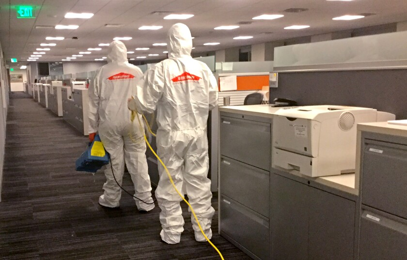 A crew disinfects a workplace in L.A. County in March due to coronavirus concerns.