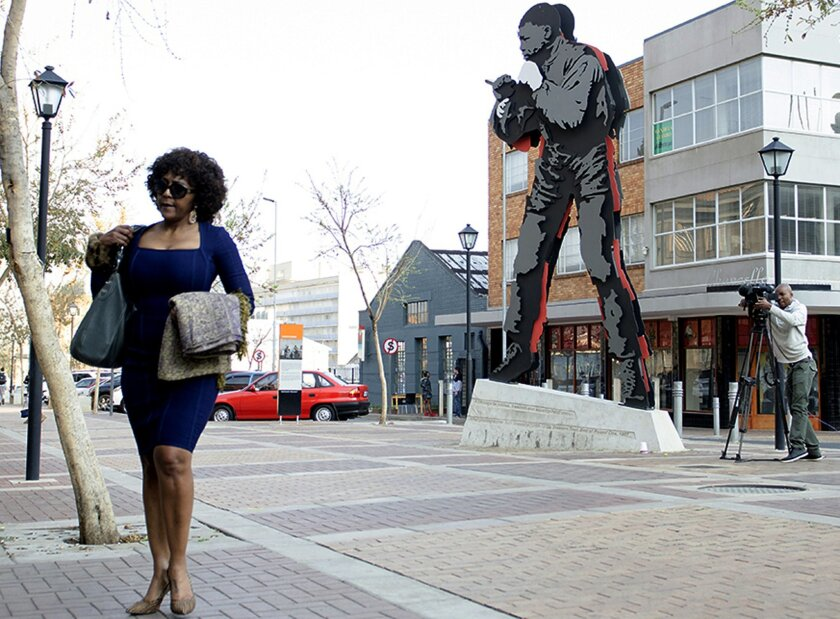 Ndileka Mandela, eldest granddaughter of former President Nelson Mandela, statue back, arrives at the Johannesburg Magistrates Court, Tuesday, Aug. 25, 2015 in support of a 25-year-old grandson of the former statesman who is accused of raping a minor at a Johannesburg bar. (AP Photo/Shiraaz Mohamed)
