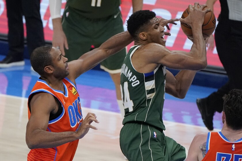 Oklahoma City Thunder center Al Horford, left, reaches for the ball from behind Milwaukee Bucks forward Giannis Antetokounmpo, right, in the first half of an NBA basketball game Sunday, Feb. 14, 2021, in Oklahoma City. (AP Photo/Sue Ogrocki)