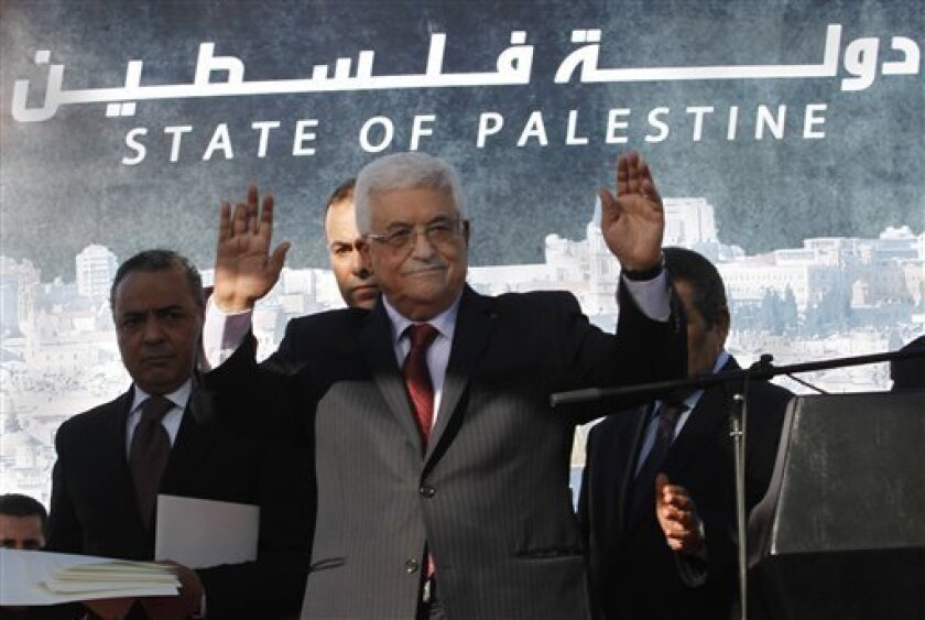 """FILE - In this Dec. 2, 2012 file photo, Palestinian President Mahmoud Abbas waves to the crowd during celebrations for their successful bid to win U.N. statehood recognition. Palestinian officials said Monday Jan. 7, 2013, they will not rush to issue new passports and ID cards with the emblem """"Stat"""