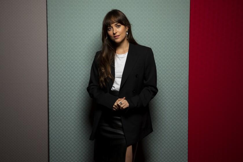 Dakota Johnson poses in a black skirt and blazer at the Toronto Film Festival