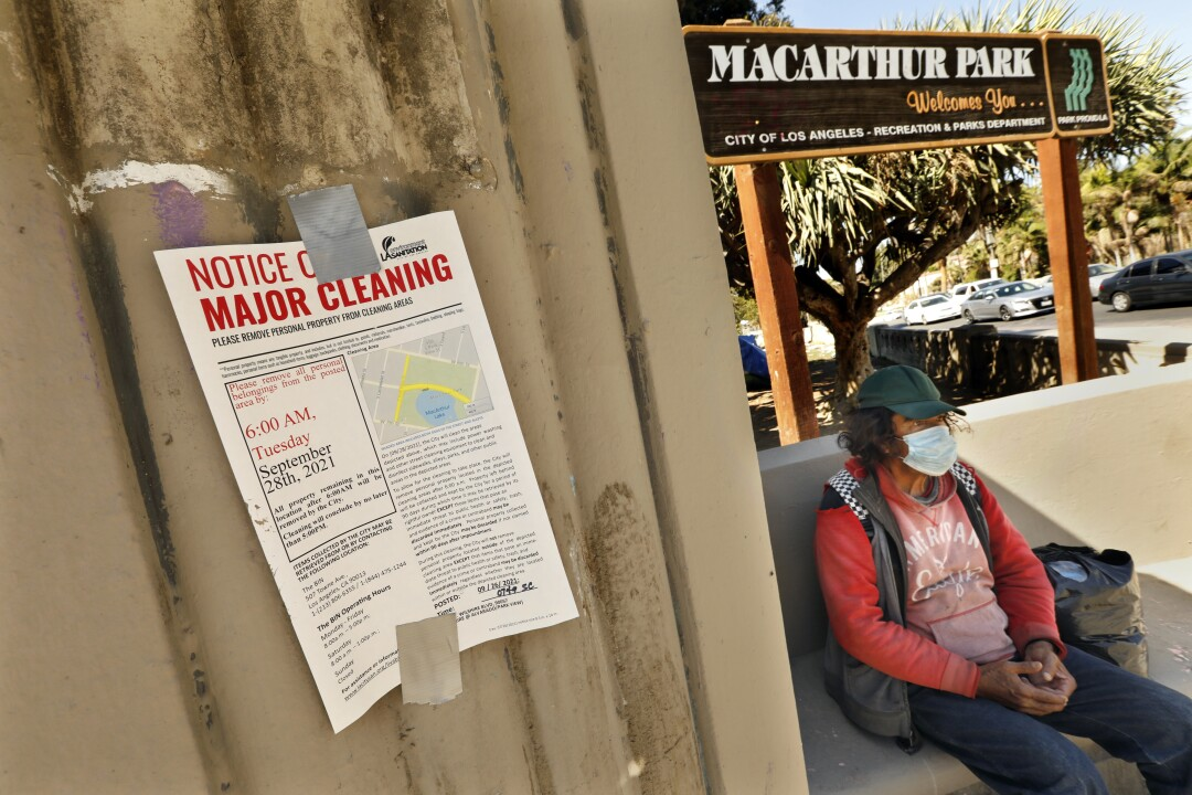 A masked person sits at MacArthur Park
