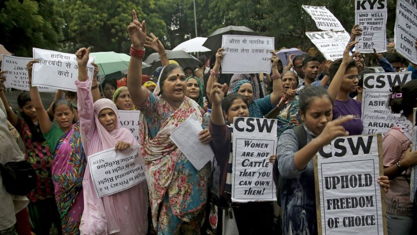 Rights activists hold placards as they shout slogans against a recent judgement by an Indian court w