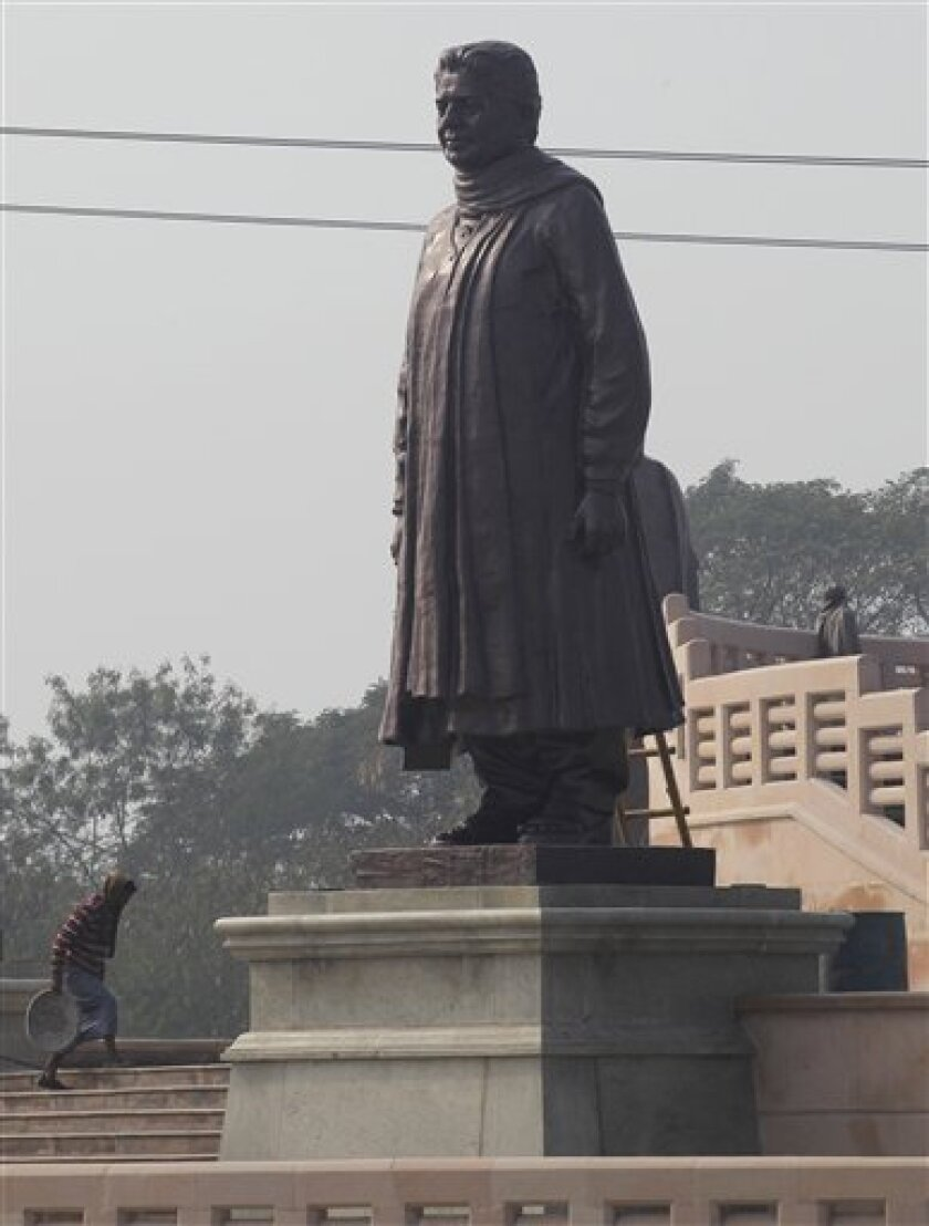 A worker walks by a statue of the Chief Minister of Uttar Pradesh, Mayawati, at a park in Noida, Uttar Pradesh, India, Monday, Jan. 9, 2012. Workmen carting truckloads of cloth raced Monday to comply with election regulations and cover up a dozen gigantic statues that a flamboyant Indian chief minister had erected of herself. India's Election Commission said the massive statues of Mayawati, who uses one name and is a hero to the country's lowest castes, were built using public money and their display violated the rules for next month's election in her Uttar Pradesh state. (AP Photo/Saurabh Das)
