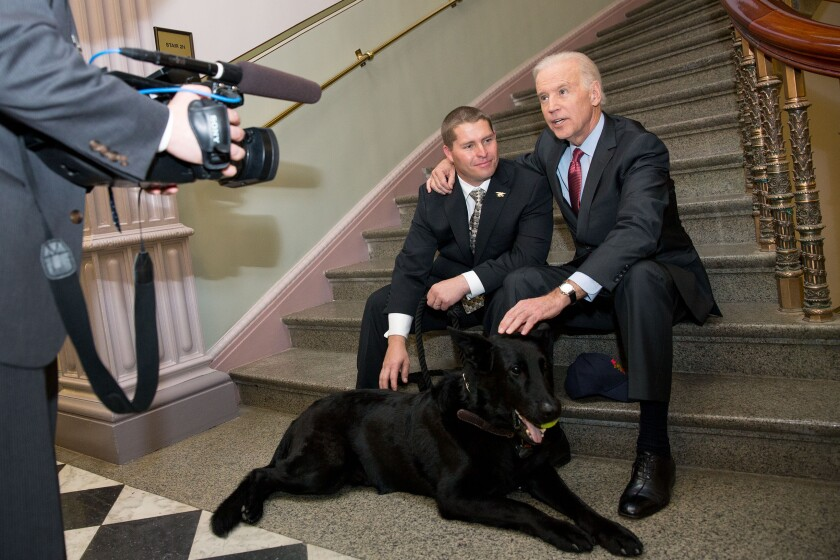 "Then-Vice President Joe Biden met with SEAL dog ""Chopper"" and his handler, Trevor Maroshek, a Navy SEAL Veteran, in the Eisenhower Executive Office Building, April 8, 2014."