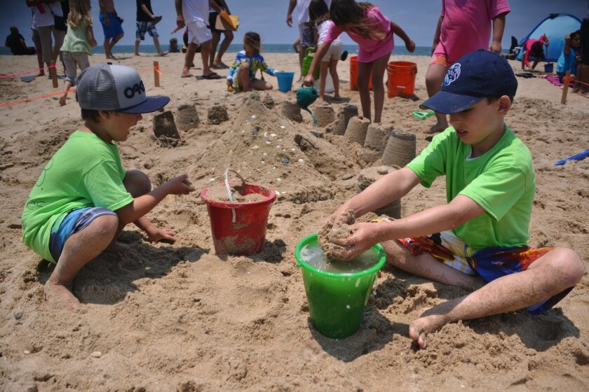 Richie Robyn, 7, and Jaxson Pate, 7, create towers out of sand for their sand castle team I.B. Someones Grandkids. Pate and Robyn were participating in the Kids and Kastles competition during the Imperial Beach Sun & Sea Festival.