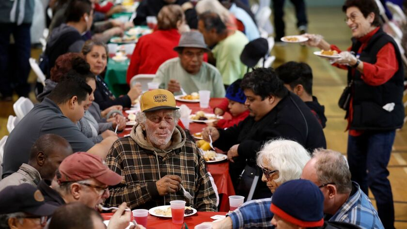 Homeless people and families in need gather at the Hollywood United Methodist Church for a free holiday meal, clothing and toys.
