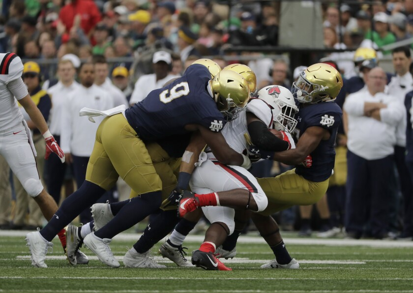FILE - In this Sept. 8, 2018, file photo, Notre Dame's Daelin Hayes (9) and cornerback Julian Love, right, tackle Ball State running back Caleb Huntley, center, during the first half of an NCAA college football game in South Bend, Ind. No. 4 Notre Dame heads into Saturday night's, Nov. 7, 2020, showdown against No. 1 Clemson allowing just 10.3 points per game. (AP Photo/Nam Y. Huh, File)
