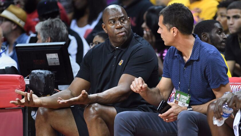 Lakers president of basketball operations Magic Johnson and general manager Rob Pelinka sit courtside at Thomas and Mack Center for the Summer League opener against the Clippers.
