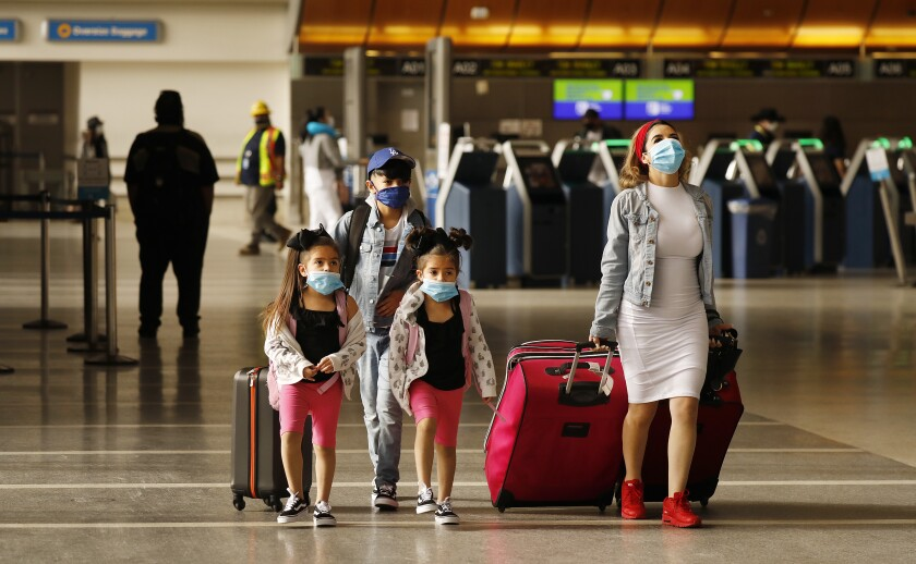 Travelers in an airport wearing face masks.