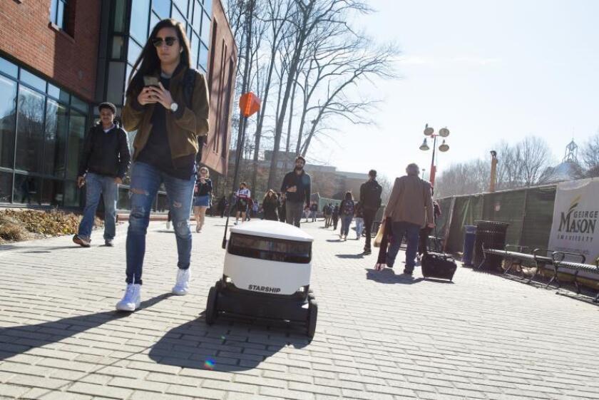 Fotografía sin fechar cedida por Starship donde se muestra un robot de Starship Technologies mientras entrega comida junto a unos transeúntes en el campus de la Universidad George Mason, en Virginia (EE.UU.). EFE/Evan Cantwell/SÓLO USO EDITORIAL/NO VENTAS