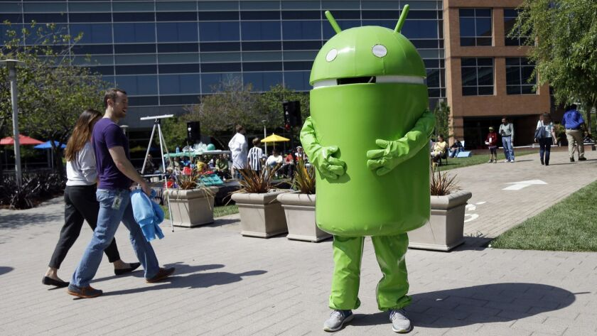 A person costumed as the Android operating system mascot stands at the Google headquarters in Mounta