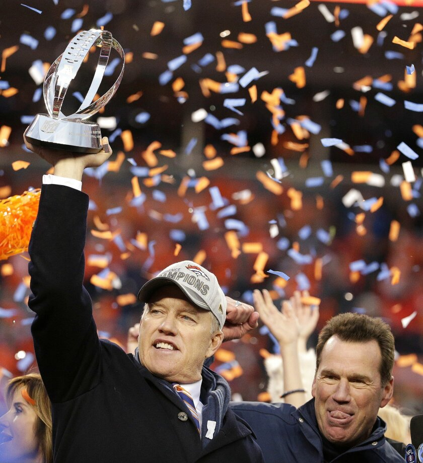 Denver Broncos general manager and executive vice president of football operations John Elway, left, is flanked by head coach Gary Kubiak as he holds the AFC Championship trophy following the NFL football AFC Championship game between the Denver Broncos and the New England Patriots, Sunday, Jan. 24, 2016, in Denver. The Broncos defeated the Patriots 20-18 to advance to the Super Bowl. (AP Photo/Charlie Riedel)