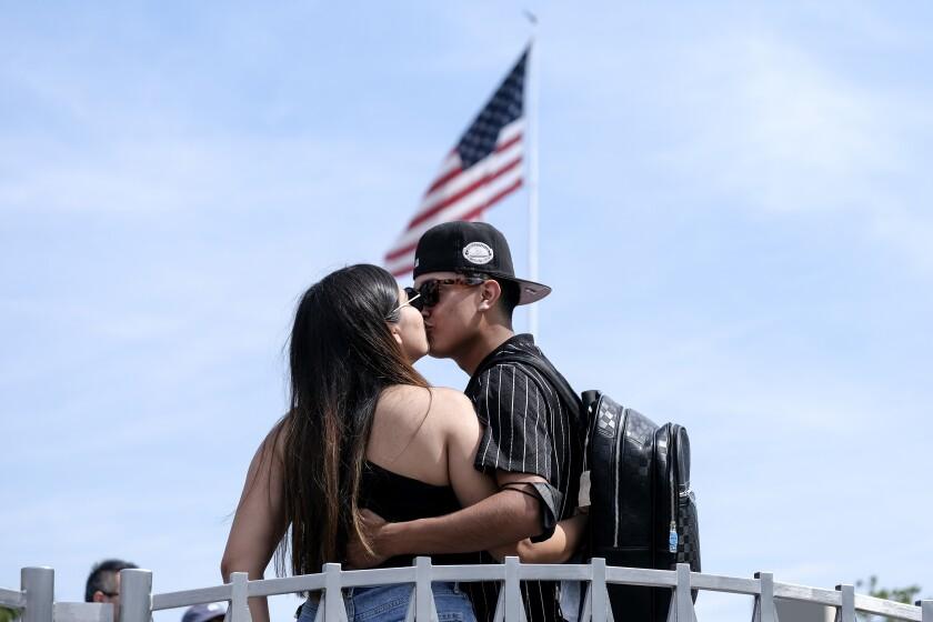 Silvia Guillen, de 19 años, y su novio Joseph Alvarez, de 22 años, ambos de El Paso, Texas, se besan en los Universal Studios en Universal City, California, el martes 15 de junio de 2021. (AP Foto/Ringo H.W. Chiu)