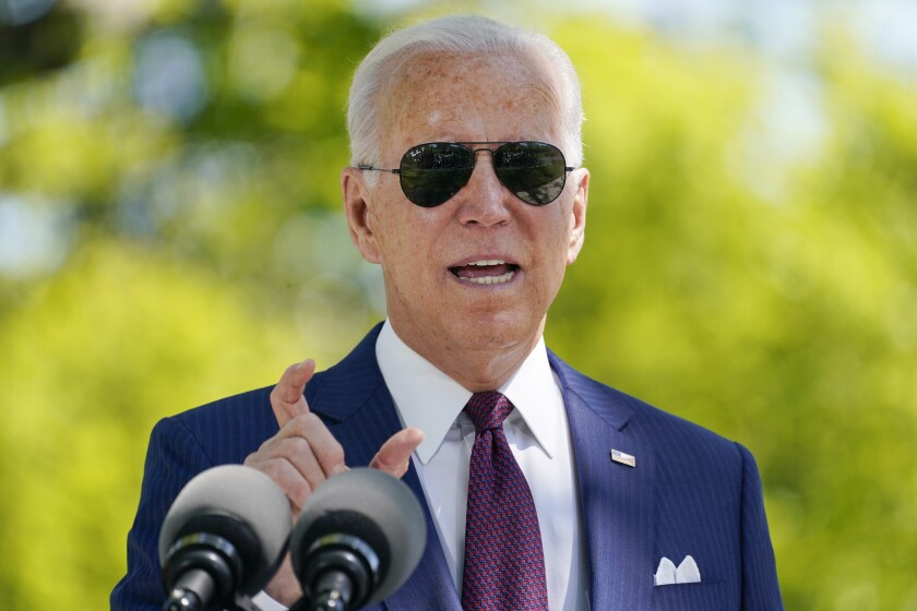 President Biden, in sunglasses, answers a question