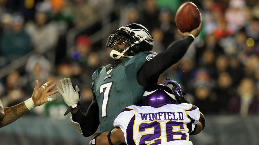 Vikings' Antoine Winfield (26) tackles Michael Vick (7) of the Philadelphia Eagles late in the first half of the last NFL game to be played on a Tuesday.