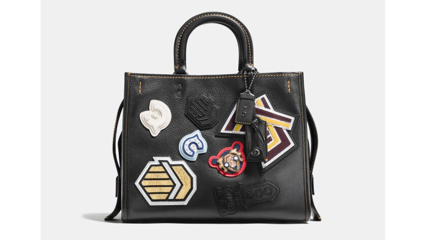 """Sport-inspired varsity patches update the """"Rogue"""" handbag in plump pebble leather with many thoughtful details, including a luxe suede lining, an interior kisslock pocket and detachable shoulder straps; $895 at the Grove and Rodeo Drive stores."""