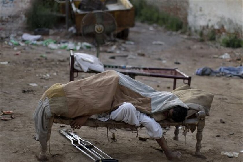 Pakistani guards of an entertainment park, sleep on a bed next to the site on the outskirts of Islamabad, Pakistan, Monday, July 4, 2011. (AP Photo/Muhammed Muheisen)