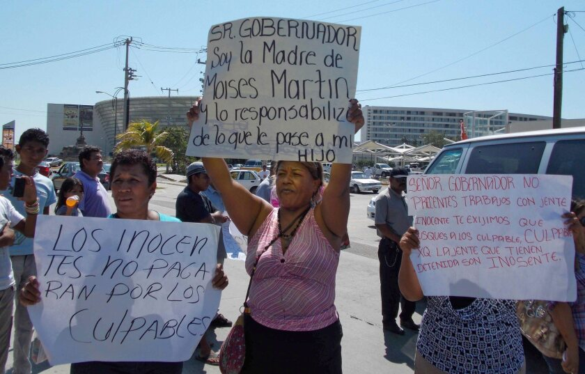 Relatives of six people arrested near Acapulco on suspicion of raping a group of Spanish citizens protest Sunday with banners proclaiming the men's innocence.
