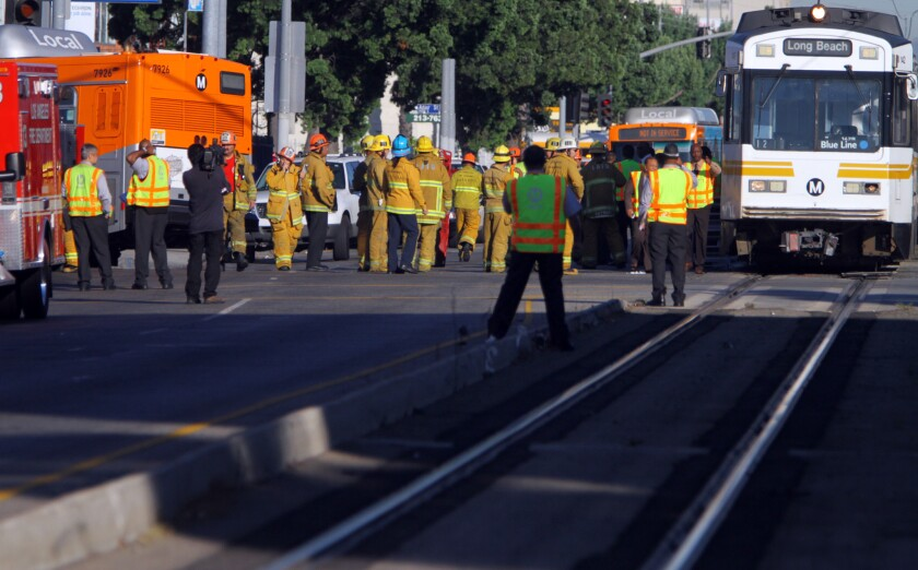 Fire officials gather at the site of a collision between a Metro Blue Line train and a bus in downtown Los Angeles in August 2012, which injured 31 people. Blue Line trains ran red lights 52 times from 2011 to 2014.