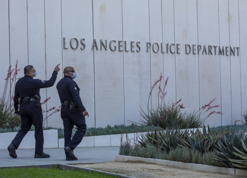 """Two men in uniform and masks walk past a building with the sign """"Los Angeles Police Department."""""""