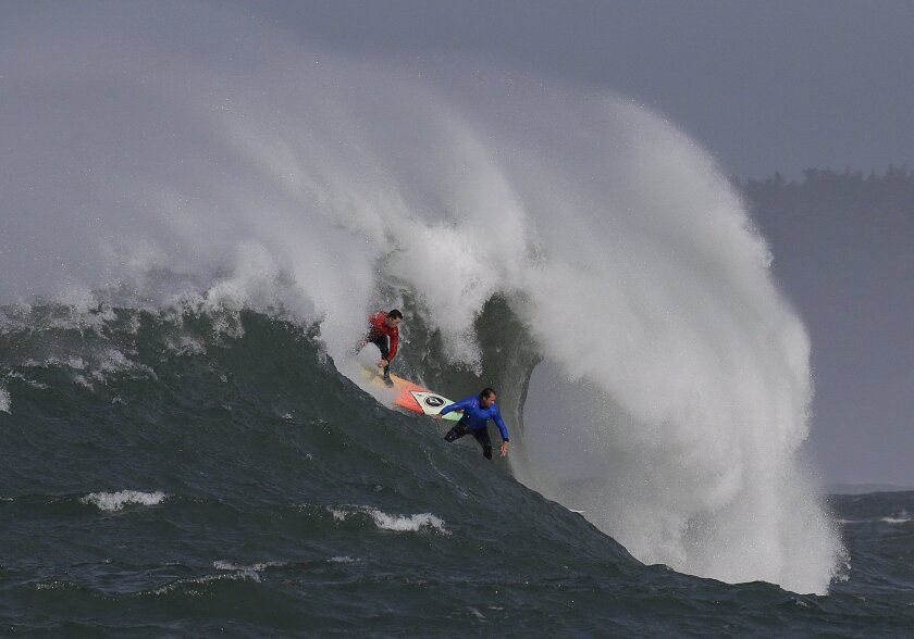 Ken Collins, left, and Chris Bertish surf a giant wave during the second heat of the Mavericks surfing contest Friday, Feb. 12, 2016, in Half Moon Bay, Calif. (AP Photo/Ben Margot)