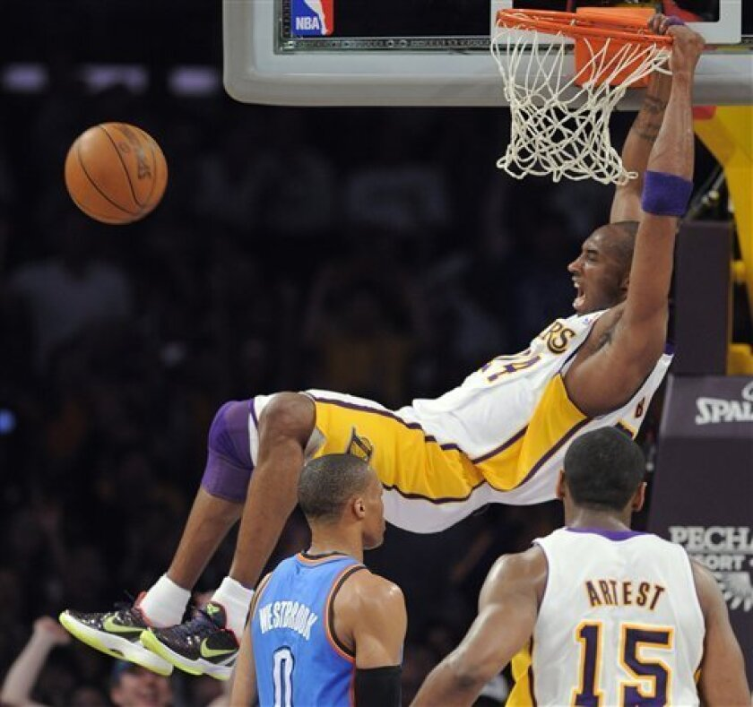 Los Angeles Lakers guard Kobe Bryant, top, dunks as Oklahoma City Thunder Russell Westbrook, left, and Lakers forward Ron Artest look on during the first half of an NBA basketball game, Sunday, April 10, 2011, in Los Angeles. (AP Photo/Mark J. Terrill)