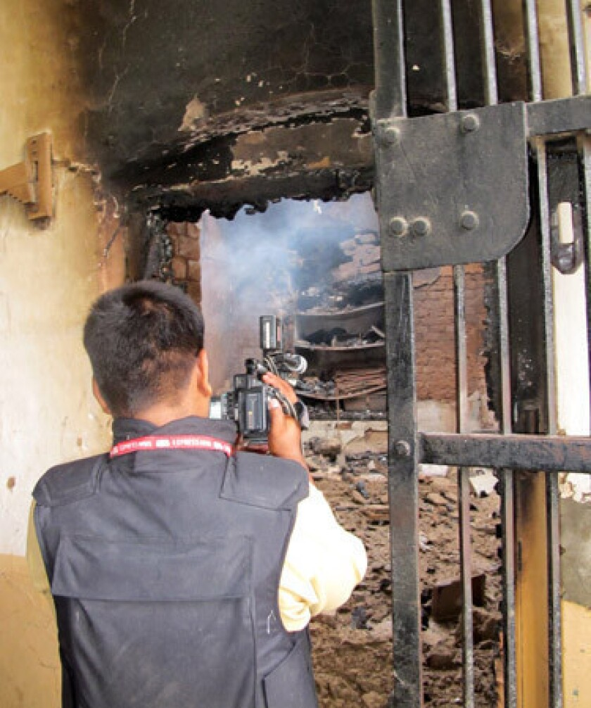 A Pakistani journalist records video of the Dera Ismail Khan central jail after it was attacked by Taliban militants.