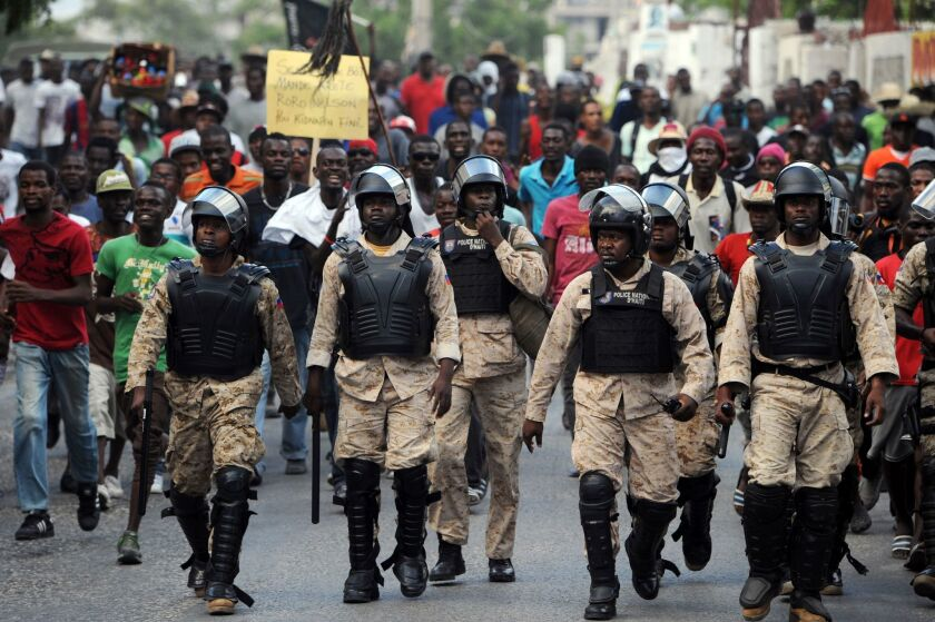 Haitian police patrol the street during a protest in Port-au-Prince on Monday.
